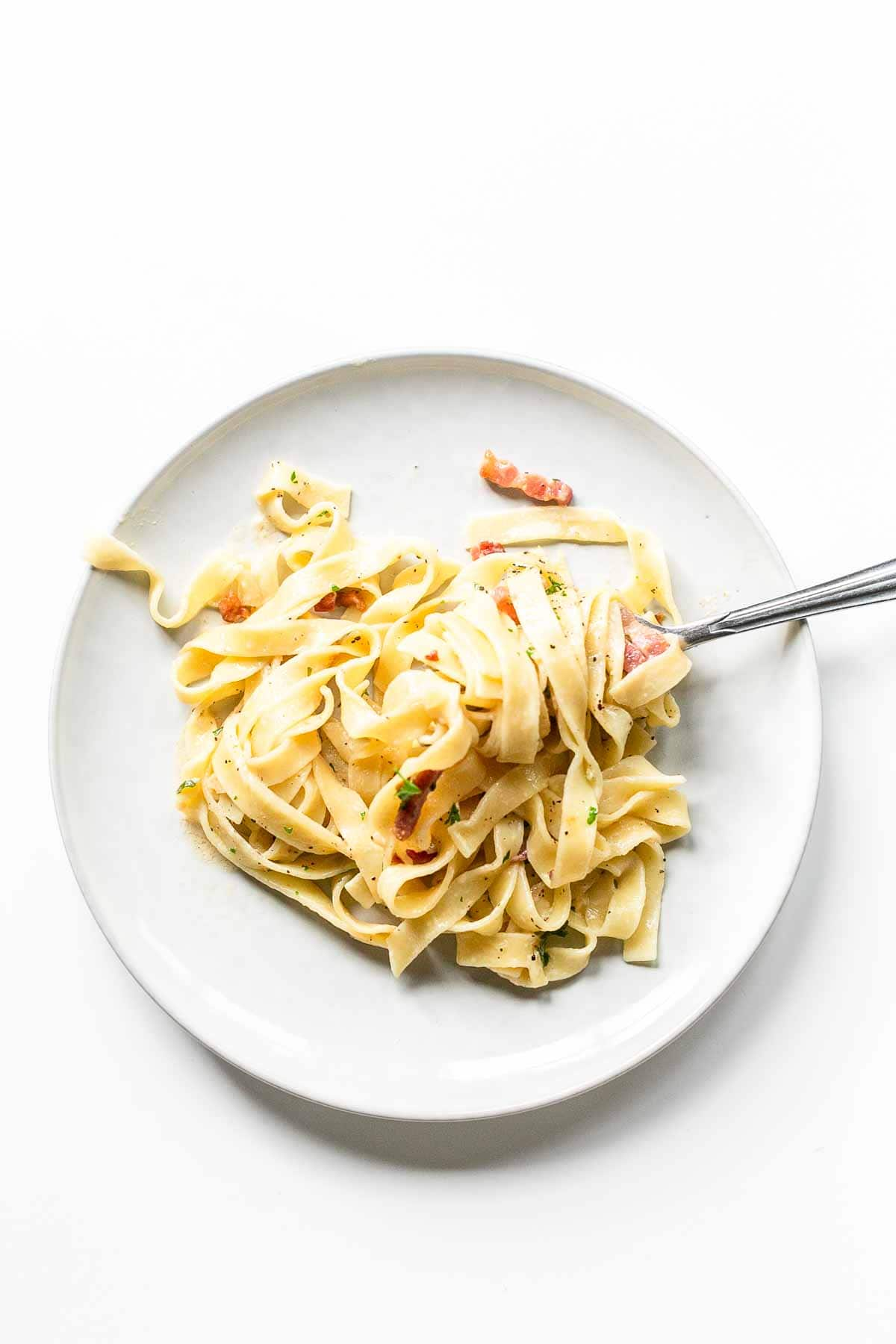 Creamy tagliatelli with bacon is a fast recipe that you have on the table in less than 15 minutes. Super delicious and a great creamy pasta dinner. Visit fastfoodbistro.com for the full recipe #fastfoodbistro #creamypasta #creamytagliatelle #pastadinner #dinner #pasta