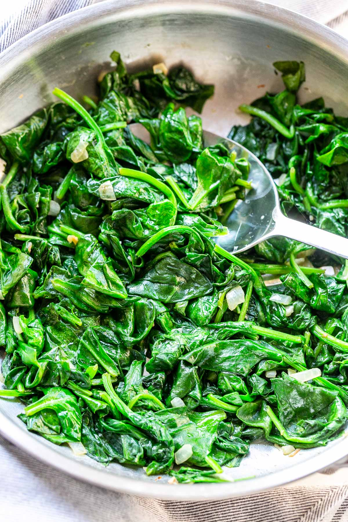 Looking for an easy way to cook spinach? Try this easy how to cook spinach recipe! Sauteed in a big skillet and serve as a tasty side dish. Visit fastfoodbistro.com for the full recipe #fastfoodbistro #spinach #howtocookspinach #sidedish #vegetablesidedish