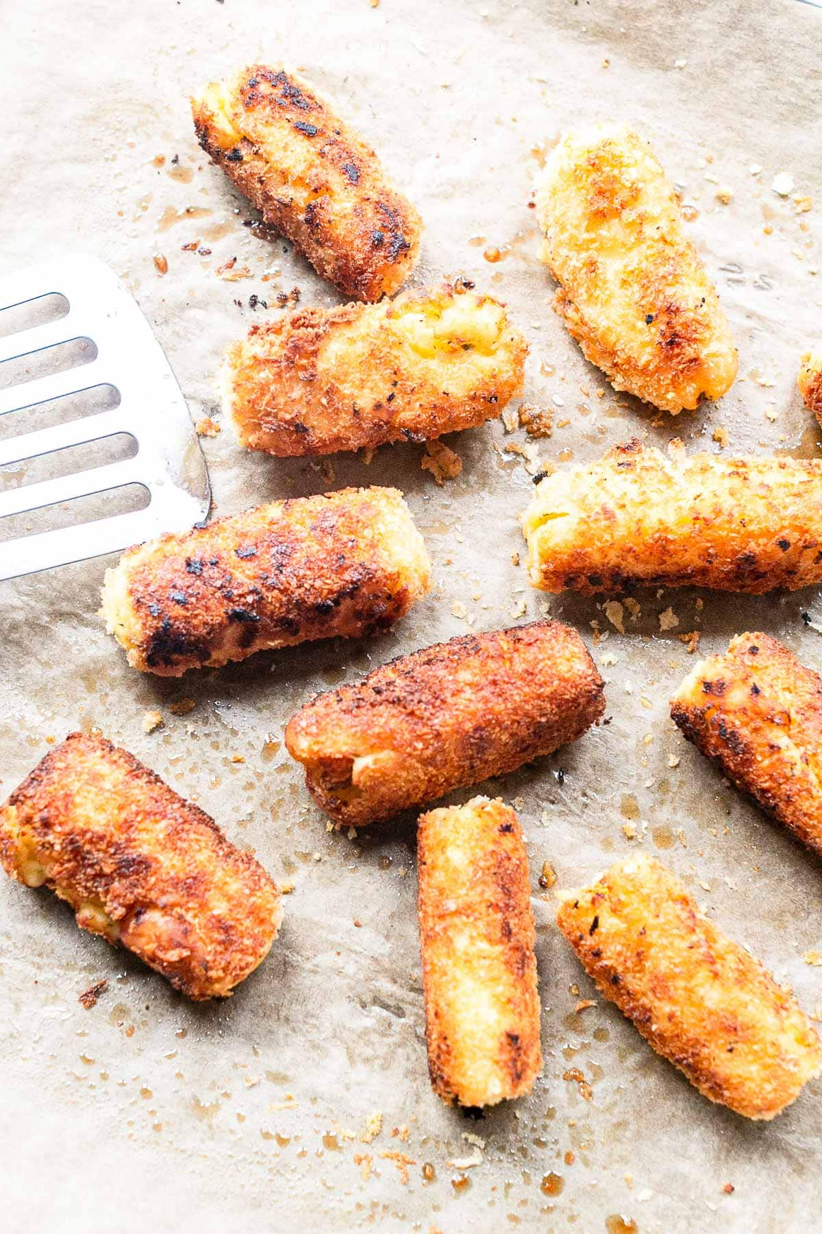 These potato croquettes are a classic side dish. The perfect combination of a crunchy outside and a soft inside! Bake in the oven or shallow fry in a skillet. Visit fastfoodbistro.com for the full recipe #fastfoodbistro #potatocroquettes #croquettes #croquetrecipe #potatocroquetterecipe #sidedish